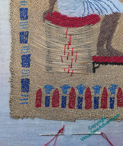 Close up of goldwork, showing gold thread tacked into place.
