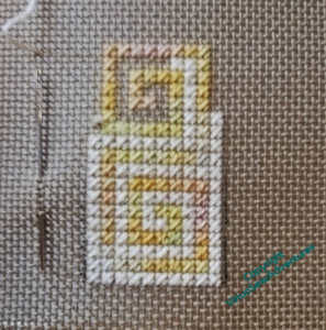 Close up of a piece of canvaswork in cream and yellow. There is a needle in the canvas beside the worked piece, which is about as high as the needle.
